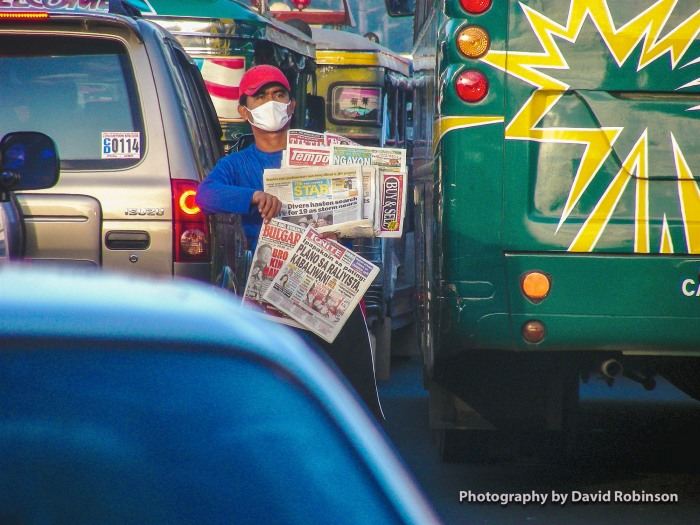 Newspaper vendor in the midst of Manila Traffic