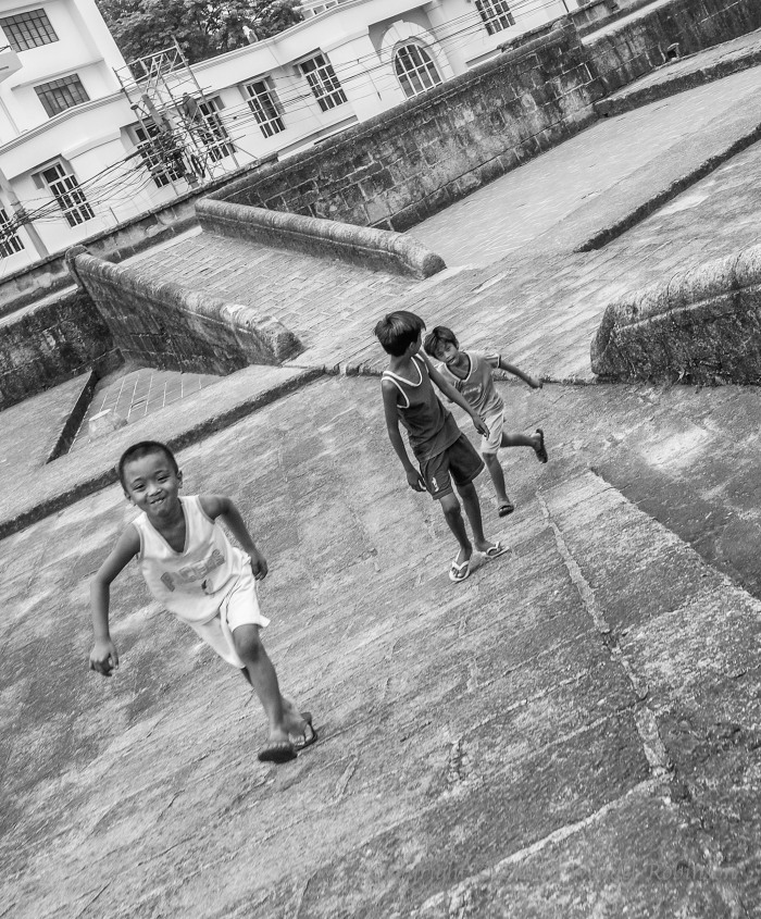 An accidental photo taken of kids running. Intramuros, the walled city of manila. Converted to Black and White, and cropped
