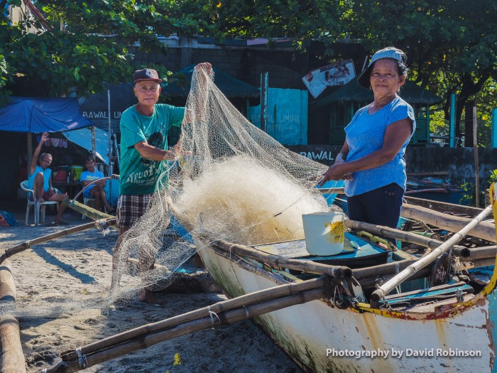 A man and woman patiently check and prepare their nets prior to going out on the bay. the go through the nets, checking for damage and making sure they are not tangled.